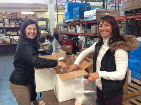 Volunteers smile as they help pack care kits for local women in need.