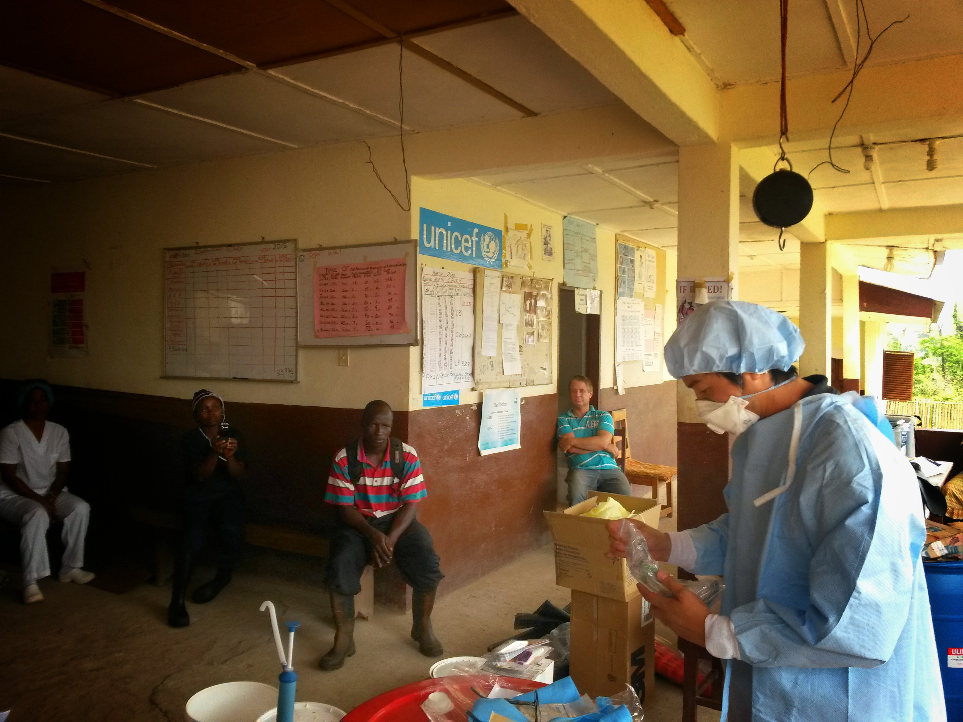 Last Mile Health Medical Director John Ly shows community health workers on the frontlines of Ebola in Liberia how to use the surgical gown sets from Japan.