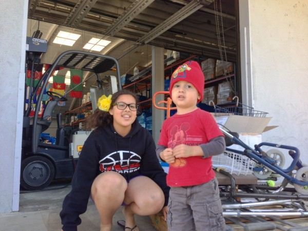 Iselle and her baby brother who inspired her project pose outside Direct Relief's warehouse while delivering orthopedic supplies she collected.