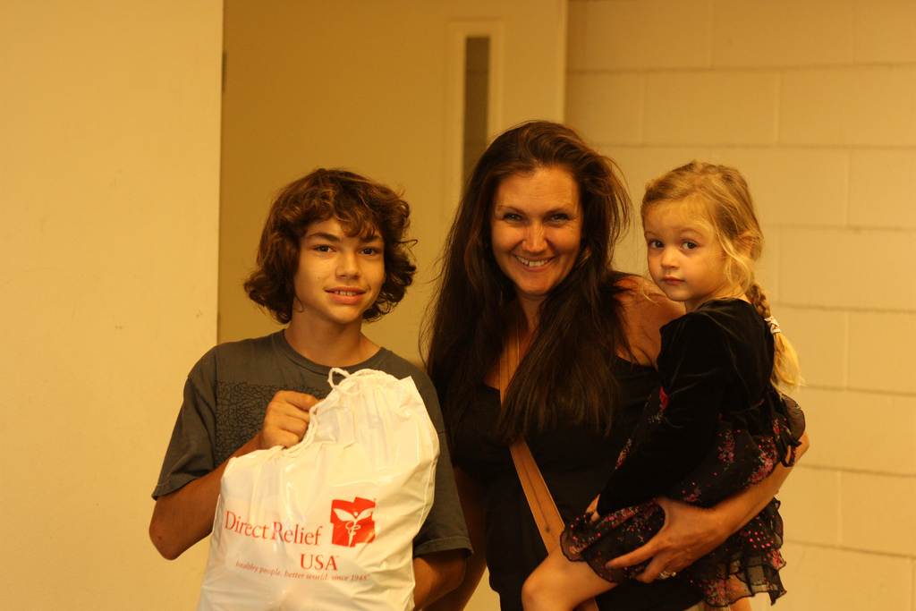 A family smiles after receiving one of our personal care packs given out at Transition House.