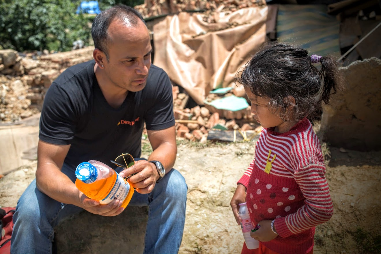 Sajan Chhetri from Direct Relief explains differences between a soft drink and Pedialyte to a local girl during a public outreach.