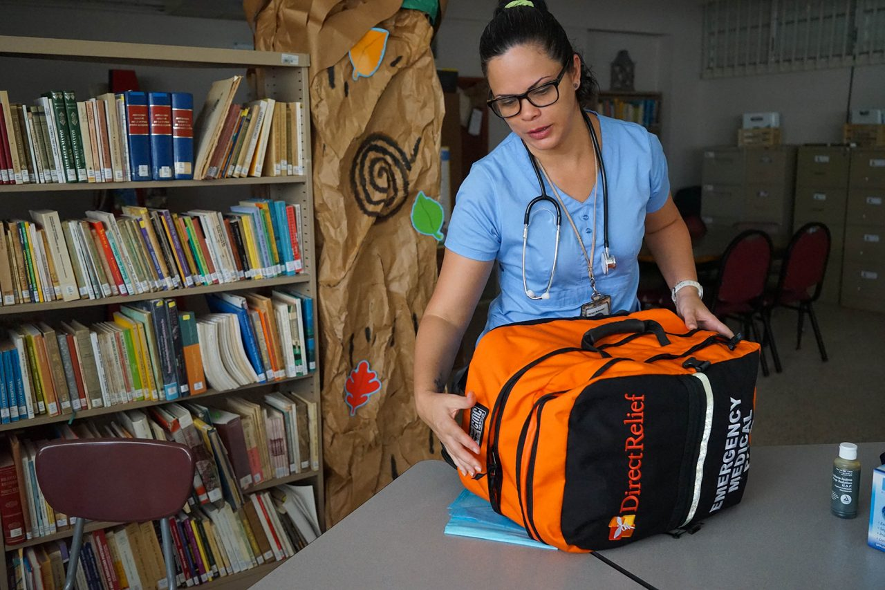 Medical staff unpack an Emergency Medical Backpack in a children's library that was transformed into a small but comprehensive medical clinic Tuesday in Coamo, Puerto Rico. (Lara Cooper/Direct Relief)
