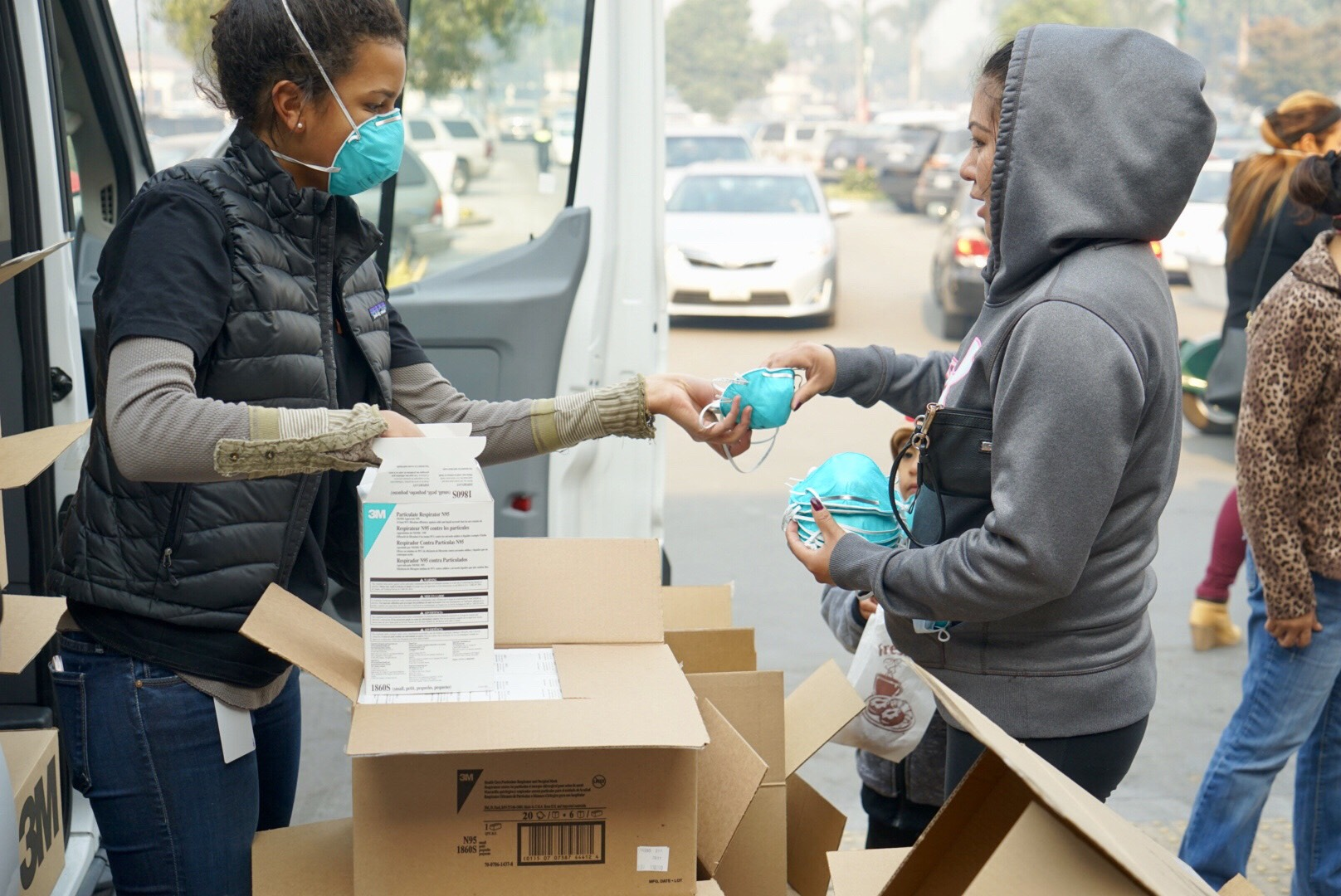 Direct Relief staffer Bryn Blanks distributes breathing masks in Carpinteria Friday morning. More than 90,000 masks have been distributed to communities impacted by wildfires this week. (Lara Cooper/Direct Relief)