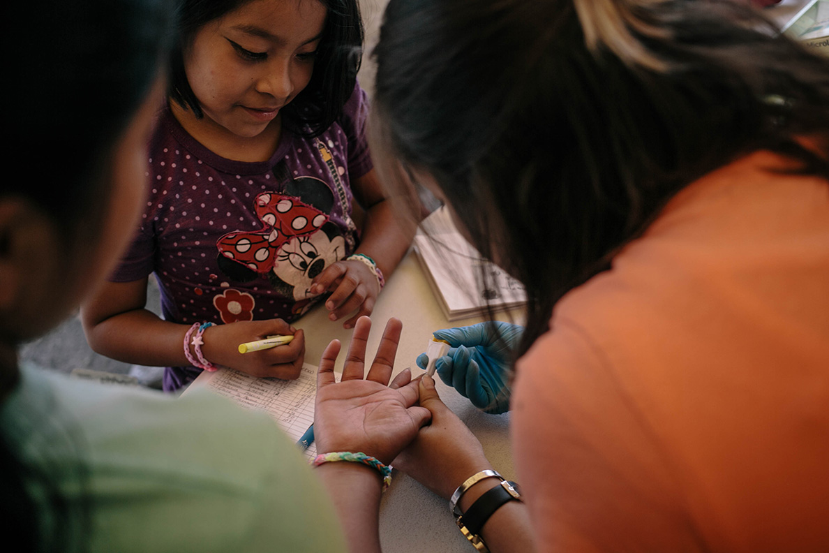 Two girls get their blood glucose levels checked at a pop-up clinic set up by the Mexican Diabetes Association in partnership with Direct Relief. The clinic, in Mexico City's neighborhood of La Roma, is aimed at serving populations in the city displaced by the earthquake, especially those with diabetes. (Photo by Meghan Dhaliwal for Direct Relief)