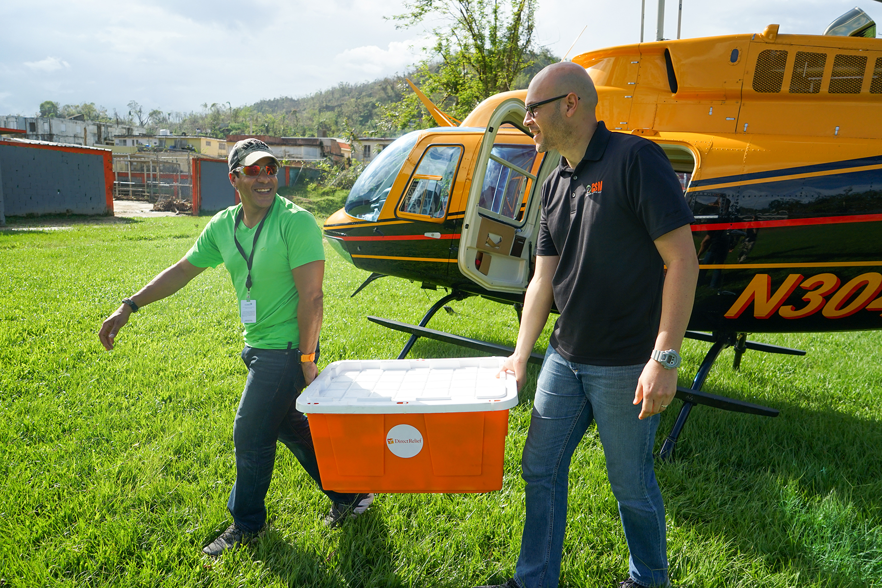 Daniel Ramos of the Puerto Rico Primary Care Association and Alexis Romero of the Corporacion de Servicios Medicos, a clinic in Utuado, unload Direct Relief medicines from a helicopter provided by Samaritan's Purse. (Lara Cooper/Direct Relief)