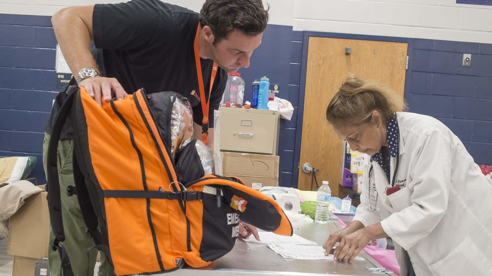 Direct Relief's Andrew MacCalla hands off an emergency medical backpack to Dr. Eileen Ramsaran, who was conducting medical care at a hurricane shelter in Panama City on Saturday, October 13, 2018.  The shelter was filled with medically vulnerable people who had been evacuated from local hospitals. (Photo by Zack Wittman for Direct Relief)